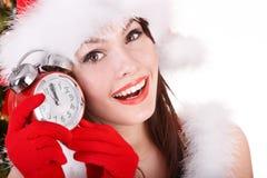 拿着时钟的圣诞老人帽子的圣诞节女孩。 免版税库存照片