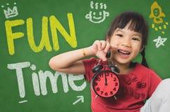 拿着时钟的女孩准备好在乐趣时间 库存照片