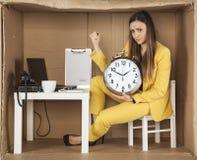 拿着时钟的女实业家,坐在一个小办公室 图库摄影