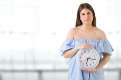 拿着时钟的女性 免版税库存照片