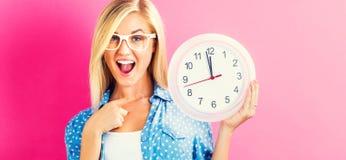 拿着时钟的妇女显示几乎12 免版税图库摄影
