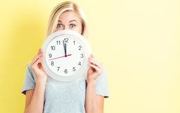 拿着时钟的妇女显示几乎12 免版税库存照片