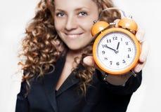 拿着时钟的新女实业家 免版税库存照片