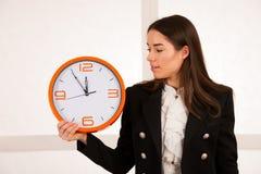 拿着时钟的逗人喜爱的妇女作为时间安排的标志 免版税库存图片