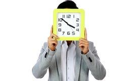 拿着时钟的年轻人盖他的面孔 免版税库存图片