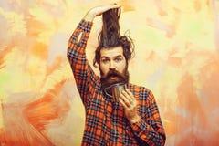 拿着时髦的边缘头发和金属杯子的有胡子的人 免版税图库摄影
