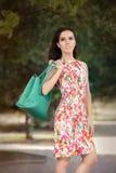 拿着时髦的钱包的花服的妇女 库存照片