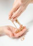 拿着昂贵的金首饰的手 免版税库存照片