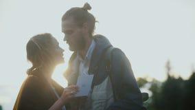 拿着明信片和读某事的年轻美好的夫妇在晚上在日落 人亲吻头的妇女 股票录像
