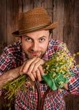 拿着春黄菊的愉快的农夫在土气木头开花 库存图片