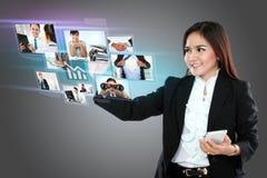 拿着智能手机和使用数字式触摸屏幕t的女实业家 免版税库存照片