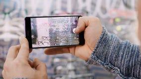 拿着智能手机和拍玻璃在眼镜师零售店,镜片的照片男性手特写镜头购物,为 影视素材