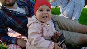 拿着智能手机和笑在自然的小女婴在手上特写镜头在夏天 免版税图库摄影