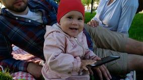 拿着智能手机和笑特写镜头的小女婴在手上 免版税库存照片