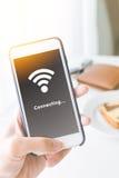 拿着智能手机和连接WiFi网络的手 免版税库存图片