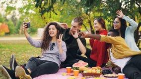 拿着智能手机和采取与朋友multiractial小组的可爱的少妇的慢动作selfie在快乐期间 影视素材