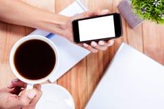 拿着智能手机和黑浓咖啡的天花板女性手 免版税库存照片