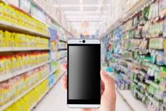 拿着智能手机有迷离超级市场背景的手 免版税图库摄影