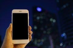 拿着智能手机有都市风景夜背景的手 免版税库存图片