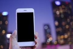 拿着智能手机有都市风景夜背景的手 免版税库存照片
