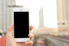 拿着智能手机有都市风景背景的手 免版税库存图片