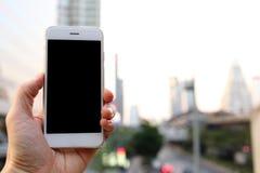 拿着智能手机有都市风景背景的手 库存照片