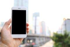 拿着智能手机有都市风景背景的手 免版税库存照片