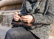 拿着智能手机的一个女孩的手和片剂和键入 免版税库存图片