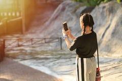 拿着智能手机的亚裔女孩,采取selfie 免版税库存图片