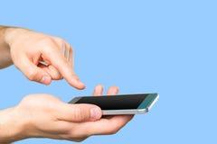 拿着智能手机的人的手 免版税库存图片