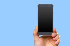拿着智能手机的人的手 免版税库存照片