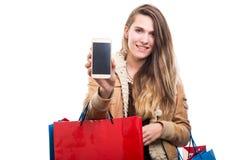 拿着智能手机的可爱的顾客女孩手中 库存照片