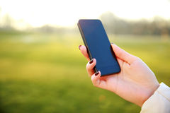 拿着智能手机的女性手 库存照片