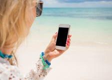 拿着智能手机的妇女手中在海滩 免版税库存图片
