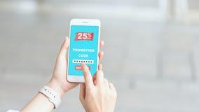 拿着智能手机的妇女键入代码从商店得到折扣 免版税库存图片