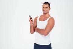 拿着智能手机的微笑的健身人 免版税库存图片