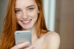 拿着智能手机的微笑的红头发人妇女 免版税图库摄影