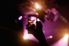 拿着智能手机的手抽象五颜六色的背景夺取图象照片和纪录录影在协调的乐曲事件 免版税库存照片