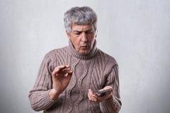 拿着智能手机的棕色毛线衣的一个困惑的成熟人设法知道如何接通它 举行sm的混乱的年长人 免版税库存图片