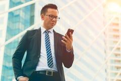 拿着智能手机的现代年轻商人穿戴黑色衣服手 专业商人常设外部办公室 免版税库存照片