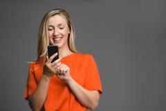拿着智能手机的年轻可爱的白肤金发的妇女 免版税库存照片