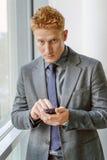 拿着智能手机的经理商人手中 免版税图库摄影
