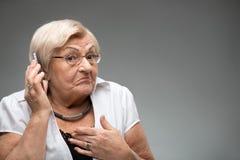 拿着智能手机的年长妇女 免版税库存图片