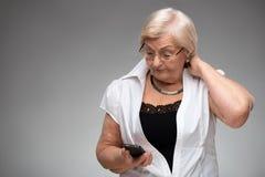 拿着智能手机的年长妇女 库存图片