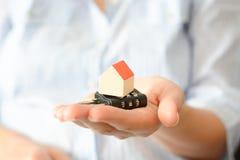 拿着暗号锁的女商人在一个微型房子下,象征住家安全或保险的概念 库存照片