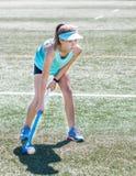 拿着曲棍的运动的女孩准备好击中曲棍球球 免版税图库摄影