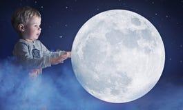 拿着月亮的一个逗人喜爱的小男孩的艺术画象 库存照片