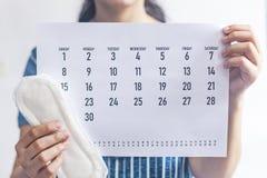 拿着月度日历和月经带的妇女 r r 期间天概念陈列 免版税图库摄影