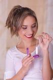 拿着月经棉花棉塞在一只手上和用她的其他手的年轻美丽的微笑的妇女塑料紫色 免版税库存照片
