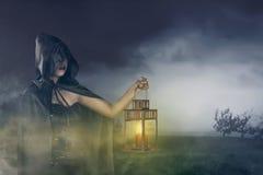 拿着有一个斗篷的美丽的亚裔巫婆女孩一个灯笼在他的 图库摄影